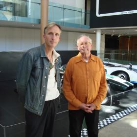 Podcast host Mark Amery standing next to interviewee and artist Billy Apple. Behind them we glimpse the nose of a vintage racing car.